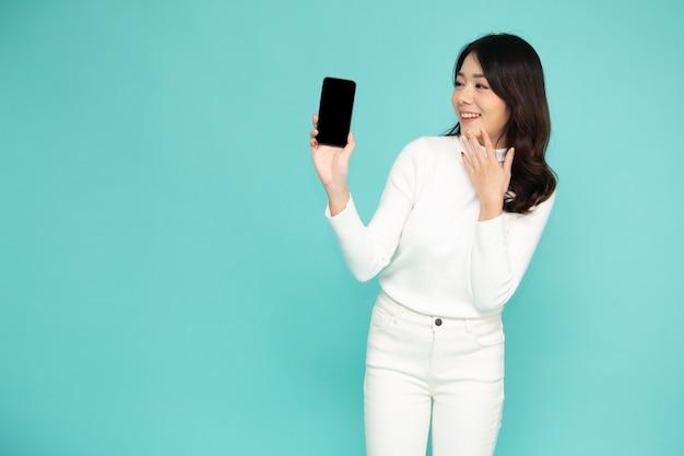 Aziatische vrouw die mobiele telefoon op hand geïsoleerde lichtgroene muur toont