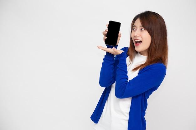 Aziatische vrouw die mobiele telefoontoepassing aan kant toont die over witte muur wordt geïsoleerd
