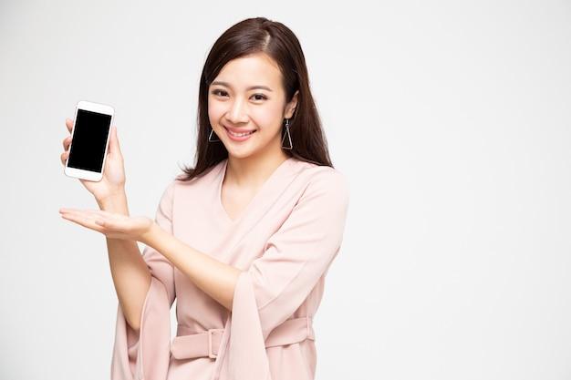 Aziatische vrouw die mobiele telefoontoepassing toont op geïsoleerde over witte muur