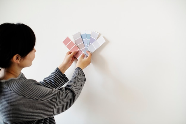 Aziatische vrouw die muurkleur kiest
