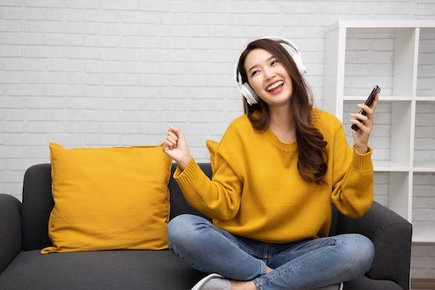 Aziatische vrouw die muziek luistert met draadloze hoofdtelefoons in de woonkamer bij condominium