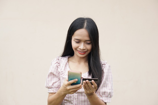 Aziatische vrouw die naar haar telefoon kijkt en blij is met online winkelen