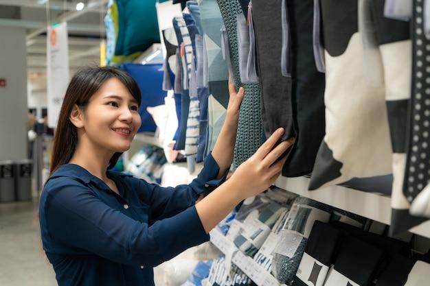 Aziatische vrouw die nieuwe hoofdkussens in de wandelgalerij kiest te kopen.