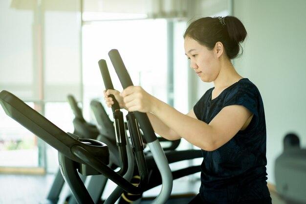 Aziatische vrouw die oefeningsmachines in binnengymnastiek met behulp van