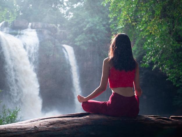 Aziatische vrouw die of yoga praktizeren doen bij de waterval