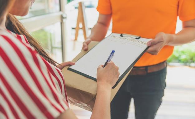 Aziatische vrouw die ontvangend pakketvakje op leveringsorderformulier ondertekent voor ontvangen volledig van leveringsman in oranje eenvormig bij haar thuis