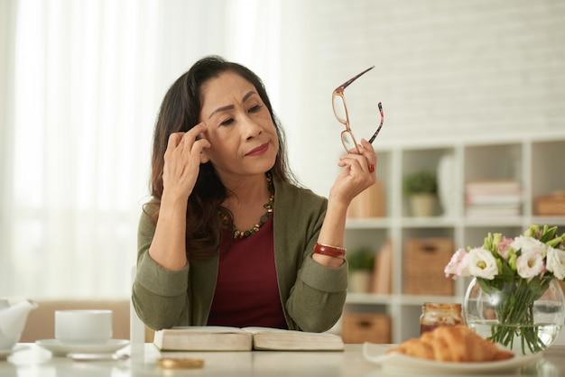 Aziatische vrouw die oogglazen opstijgen die bij lijst in ochtend zitten