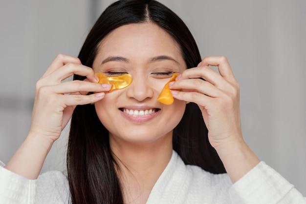 Aziatische vrouw die ooglapjes gebruikt