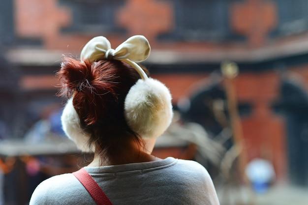 Aziatische vrouw die oorkappen in de straat draagt