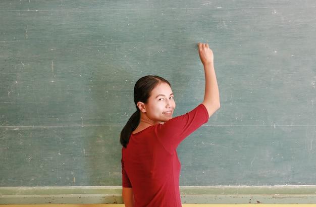 Aziatische vrouw die op bord met krijt in klaslokaal schrijft.