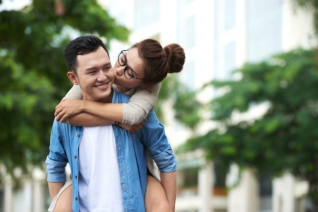 Aziatische vrouw die op de rug van rit op vriend geniet