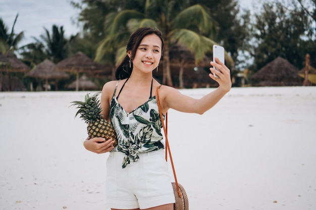 Aziatische vrouw die op de telefoon bij het strand spreekt