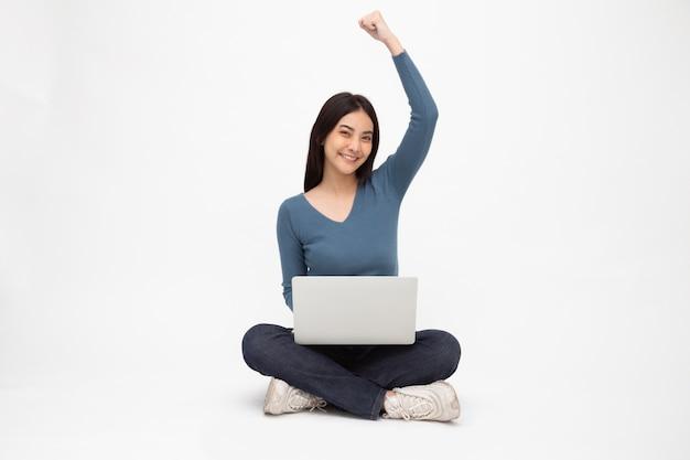 Aziatische vrouw die op de vloer zit en hand omhoog steekt en een laptop gebruikt