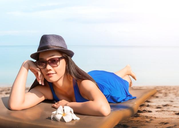 Aziatische vrouw die op het oceaanstrand zonnebaadt