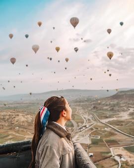 Aziatische vrouw die op kleurrijke hete luchtballons letten vliegend over de vallei in cappadocia, turkije deze romantische tijd