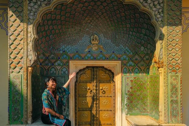Aziatische vrouw die op lotus (of de zomer) poort in het stadspaleis van jaipur in rajasthan india situeert