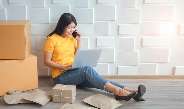 Aziatische vrouw die op zoek is naar bestelgegevens en apparatuur op laptops en mobiele telefoons controleert