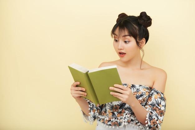 Aziatische vrouw die open boek houdt en het met uitdrukking van ongeloof op gezicht bekijkt