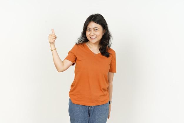 Aziatische vrouw die oranje kleurent-shirt draagt dat duimen omhoog gebaar toont dat op witte achtergrond wordt geïsoleerd