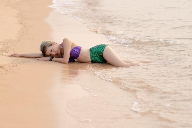 Aziatische vrouw die paars en groen meerminzwempak draagt dat op het zandstrand ligt.