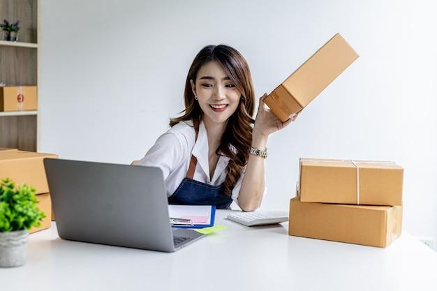 Aziatische vrouw die pakketdozen vasthoudt en berichten typt op laptop, ze is eigenaar van een online winkel, ze bevestigt bestellingen van klanten die bestellen via online sites. online verkoopconcept.