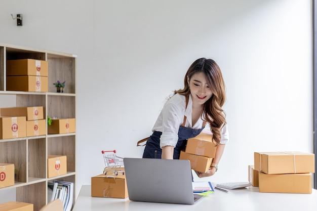 Aziatische vrouw die pakketdozen vasthoudt en bestellingen van laptop controleert, ze is eigenaar van een online winkel, ze verpakt en verzendt via een particulier transportbedrijf. online verkoop en online winkelconcepten.