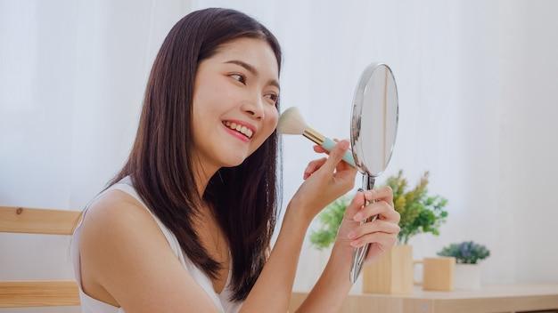 Aziatische vrouw die poeder gebruikt met borstel make-up voor de spiegel