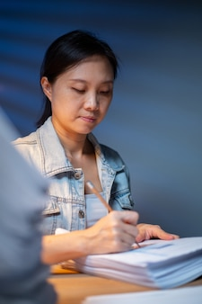 Aziatische vrouw die potlood gebruikt voor notitie over rapportfinanciën met overuren op kantoor. 's nachts laat werken voor een duidelijk document. overwerk laat werken.