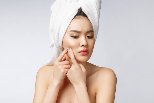 Aziatische vrouw die pukkel op gezicht bekijkt. de jonge vrouw probeert haar pukkel te verwijderen