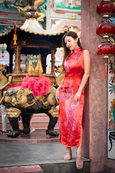 Aziatische vrouw die rode kleding cheongsam draagt bij chinees heiligdom. chinees nieuwjaar concept.