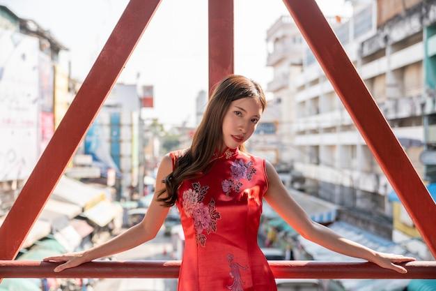 Aziatische vrouw die rode kleding cheongsam draagt bij de stad van china. chinees nieuwjaar concept.