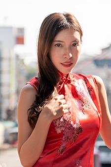 Aziatische vrouw die rode kleding cheongsam draagt bij de stad van china