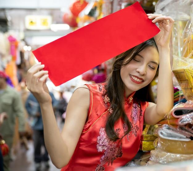 Aziatische vrouw die rode kleding cheongsam draagt die bij markt voor chinees nieuwjaar winkelt.