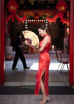 Aziatische vrouw die rode kleding cheongsam draagt en een gouden ventilator houdt bij chinees heiligdom. chinees nieuwjaar concept.