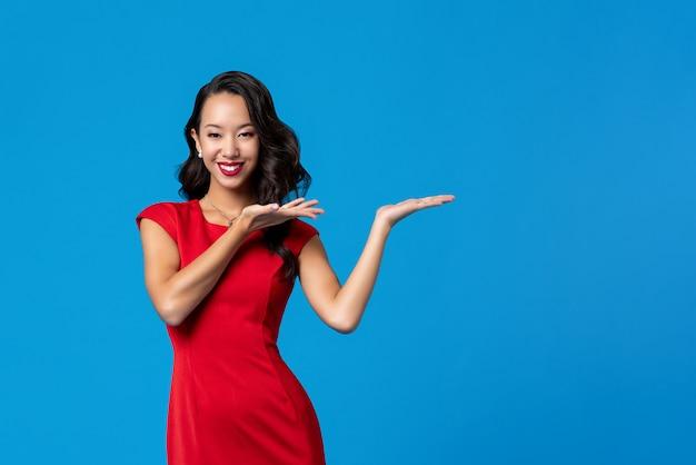 Aziatische vrouw die rode kleding draagt die voorstellend gebaar met open handen doet