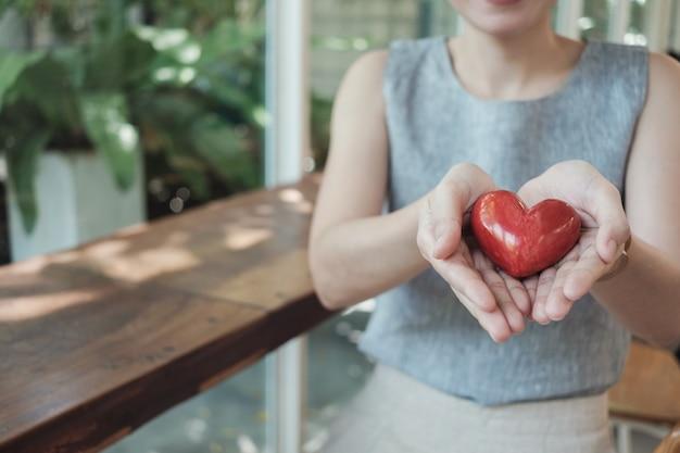Aziatische vrouw die rood hart, ziektekostenverzekering houdt