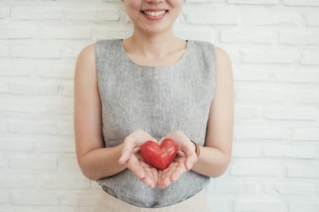 Aziatische vrouw die rood hart, ziektekostenverzekering, schenkingsliefdadigheid houdt