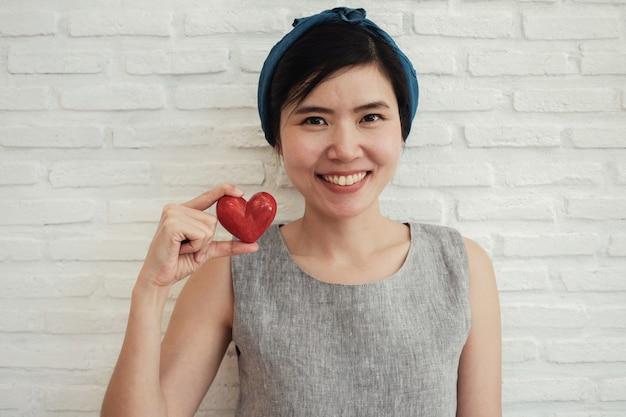 Aziatische vrouw die rood hart, ziekteverzekering, het concept van de schenkingliefdadigheid, de dag van het wereldhart houden