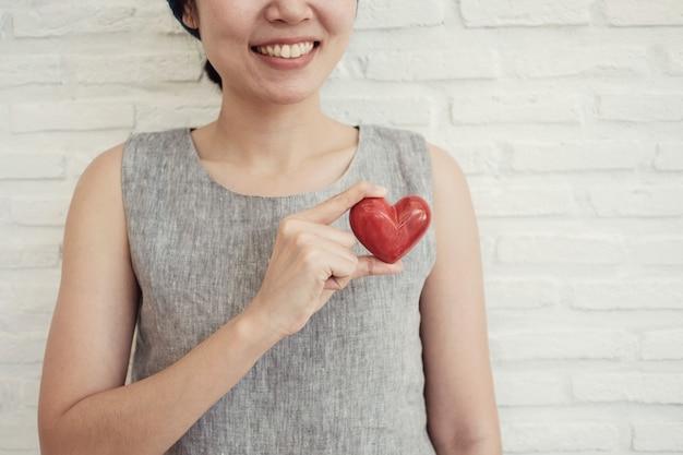Aziatische vrouw die rood hart, ziekteverzekering, het concept van de schenkingliefdadigheid houdt