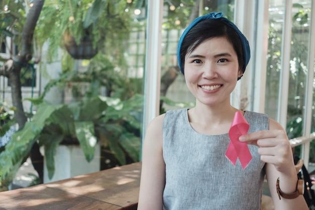 Aziatische vrouw die roze lint, de voorlichting van borstkanker, het roze van oktober houdt