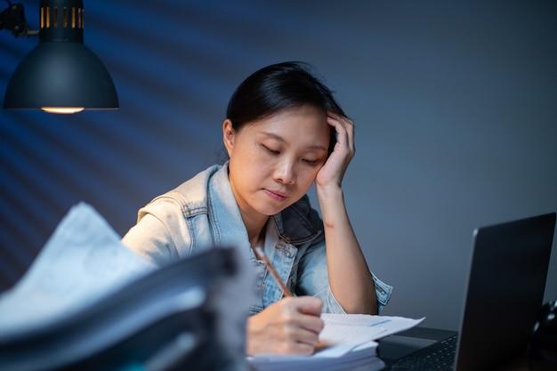 Aziatische vrouw die 's nachts in overwerk documenten schrijft.