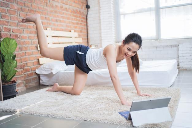 Aziatische vrouw die 's ochtends thuis traint, kijkt ze naar de instructievideo.