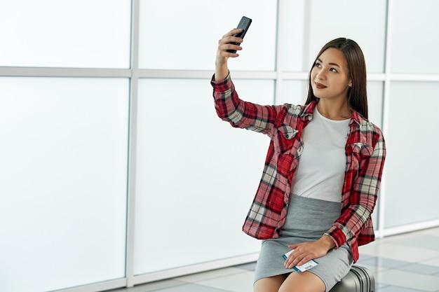 Aziatische vrouw die selfie met kaartjes maken die op vertrek in luchthaven wachten