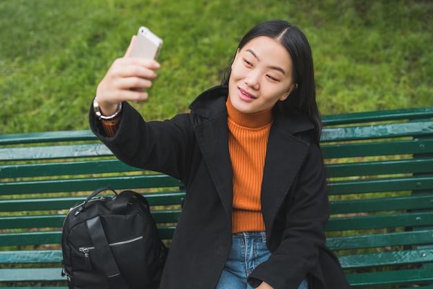 Aziatische vrouw die selfie met telefoon neemt.