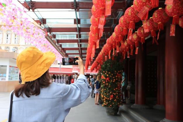 Aziatische vrouw die slimme telefoon met behulp van om een foto van chinese nieuwe jaarlantaarns in de stad van china in singapore te nemen
