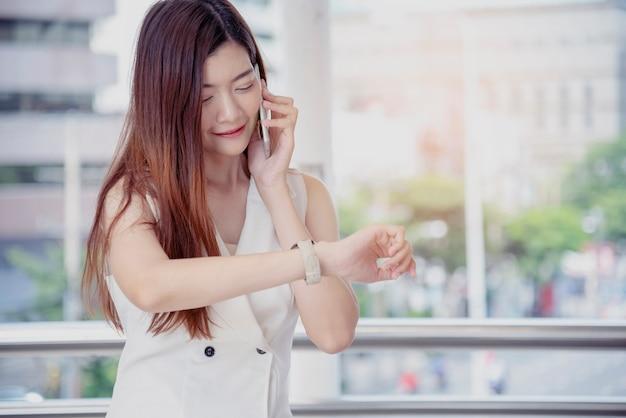 Aziatische vrouw die smartphone belt, kijkt naar het horloge. geluk aziatische vrouw met mobiele telefoon op afroep.