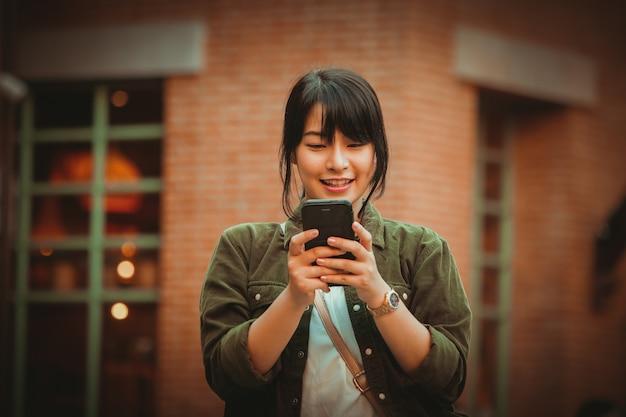 Aziatische vrouw die smartphone met gelukkige stemming in winkelcomplex gebruiken