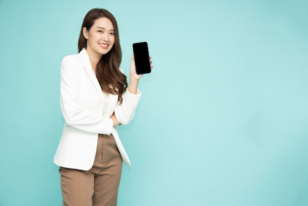 Aziatische vrouw die smartphone of mobiele telefoontoepassing toont of voorstelt die over groene achtergrond wordt geïsoleerd