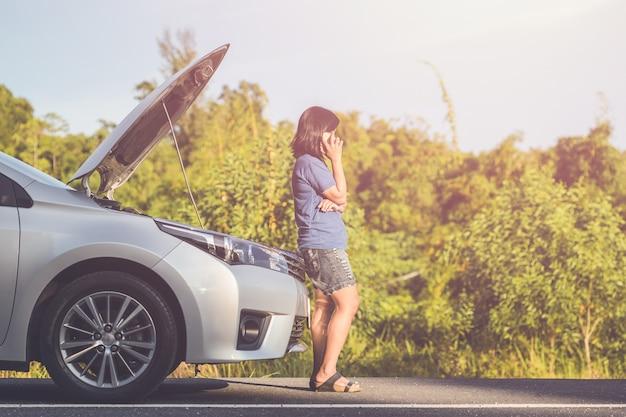 Aziatische vrouw die smartphone voor haar gebroken auto op de weg gebruiken