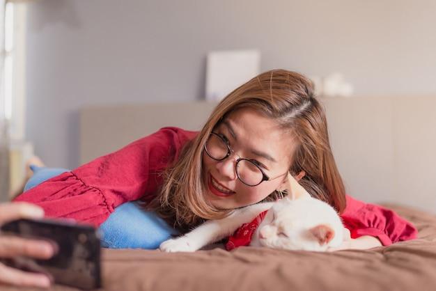 Aziatische vrouw die smartphone voor selfie op bed gebruiken
